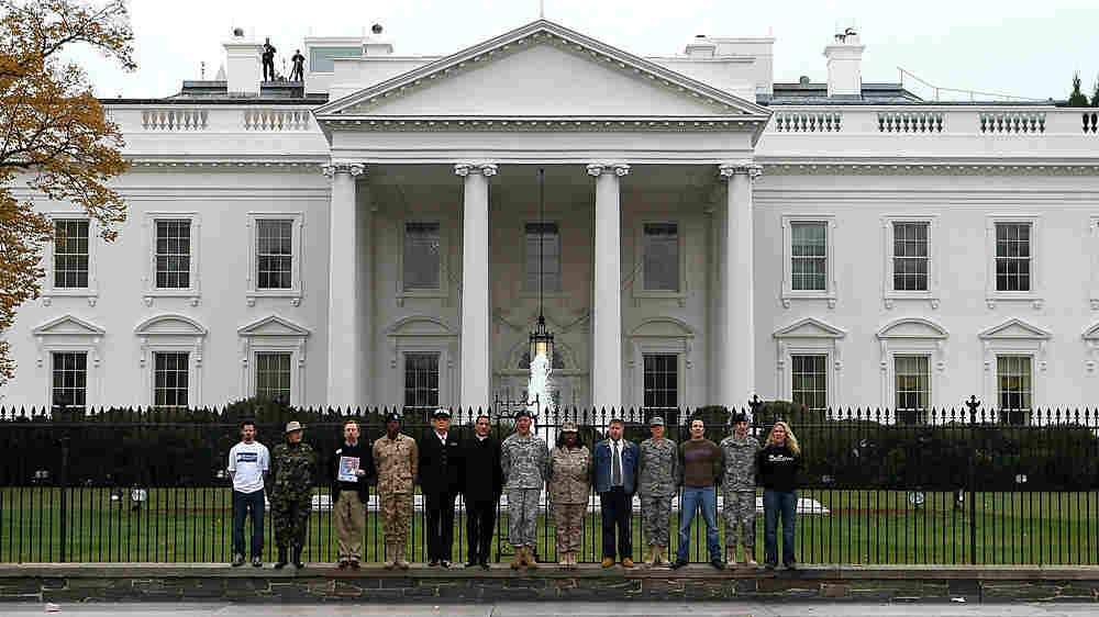 Gay-rights activists and gay veterans handcuff themselves to the fence of the White House.