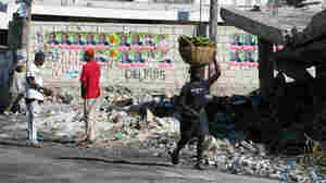 A Haitian woman walks past walls plastered with election posters