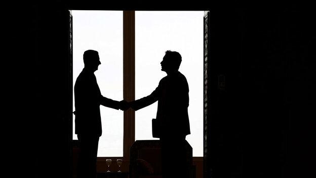 Syrian President Bashar al-Assad, left,  hands with U.S. undersecretary William Burn