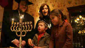 Rabbi Joshua Metzger, his wife Brocha, and their children Menachem Mendel and Sarah Perel stand by a menorah.
