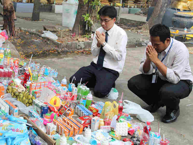Buddhists pray in front of drinks, food and toys laid out for the spirits of the fetuses