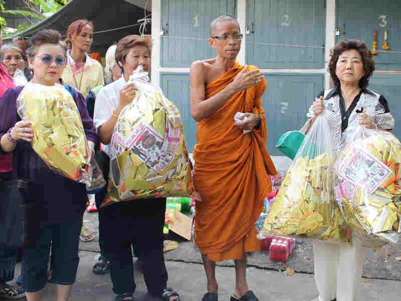 Monk Somprasong Panyavajiro stands with Buddhist followers holding paper money offerings