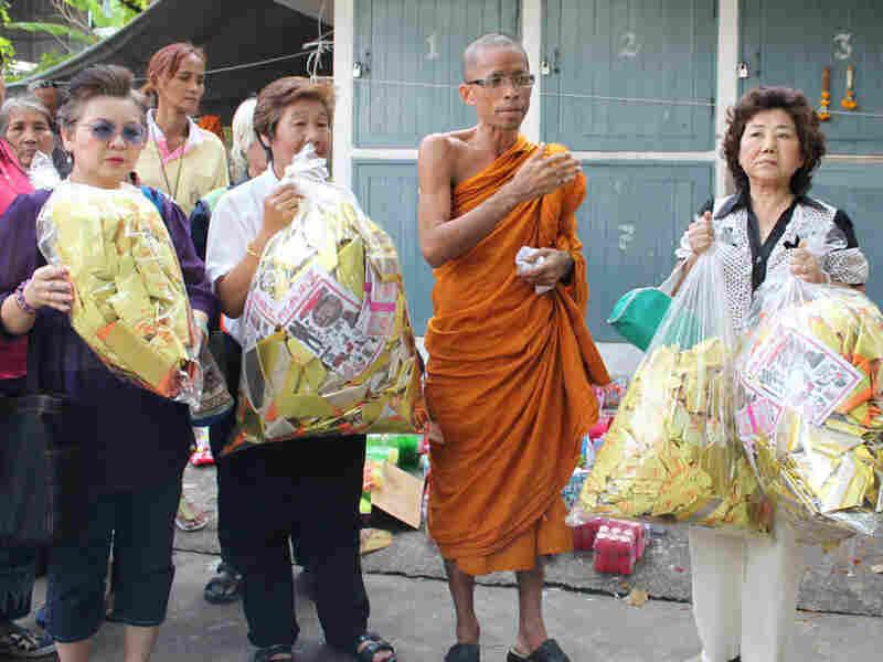 Monk Somprasong Panyavajiro stands with Buddhist followers holding paper money offerings
