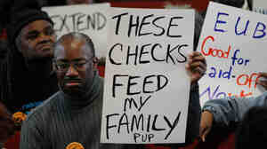 Frank Wallace, who is unemployed, displays a sign during a vigil in Philadelphia.