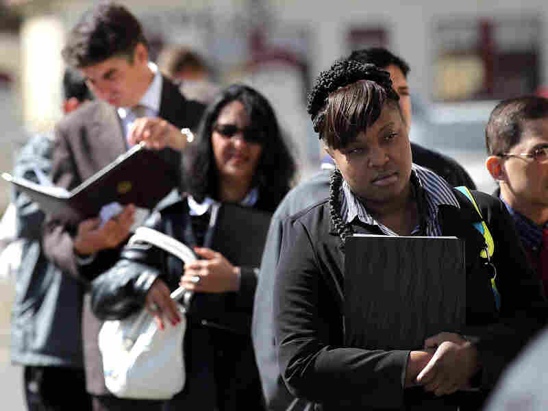 Job seekers wait in line before entering a job fair in San Francisco.