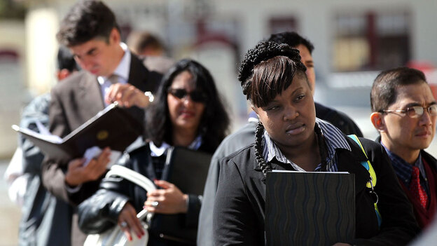 Job seekers wait in line before entering a job fair in San Francisco. Private employers added 50,000 jobs in November, down significantly from the 160,000 the previous month. (Getty Images)