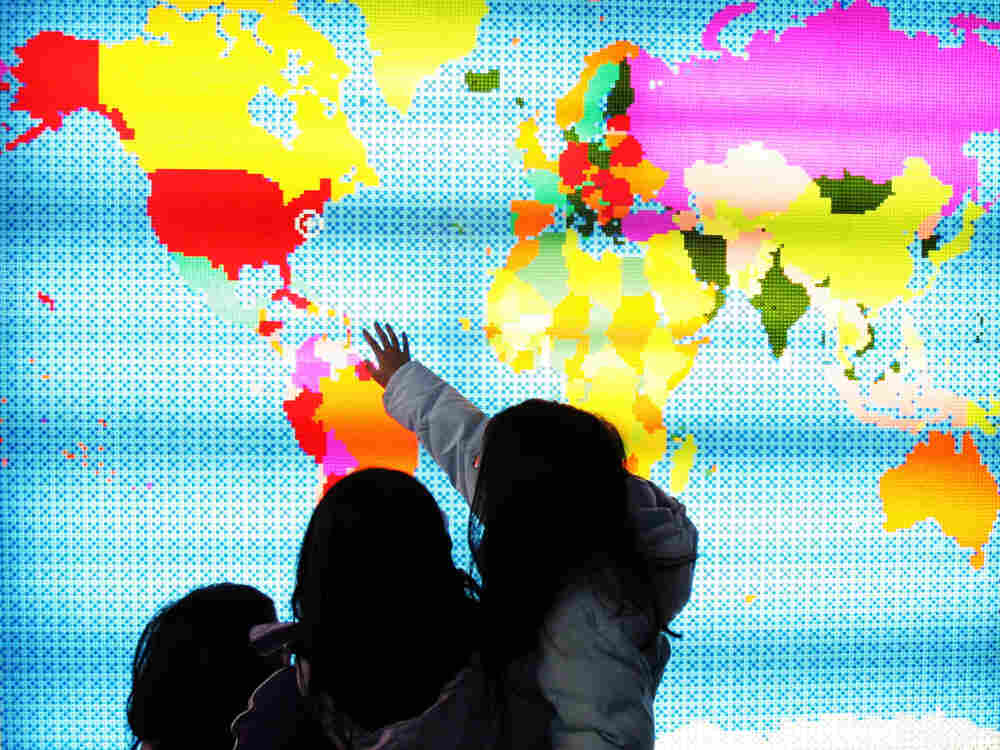 Children touching a lit up map of the world.