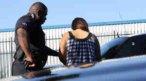 A police officer processes a young woman arrested on prostitution charges.