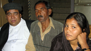 The Rev. Samson Dilawar, a Catholic priest, with Ashiq Masih, husband of Asia Bibi, and daughter Sidra  at a safe house where the family agreed to be interviewed.