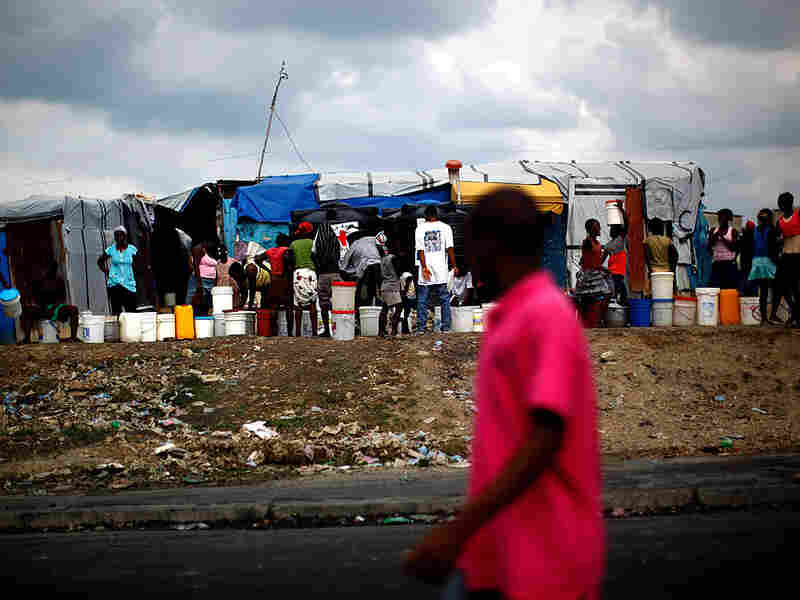 Camp residents stand in line at a water distribution site at the old military airport in Haiti