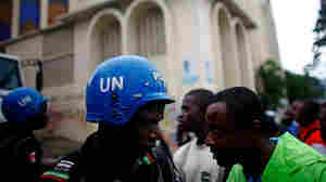 U.N. forces try to calm the crowd outside an election center