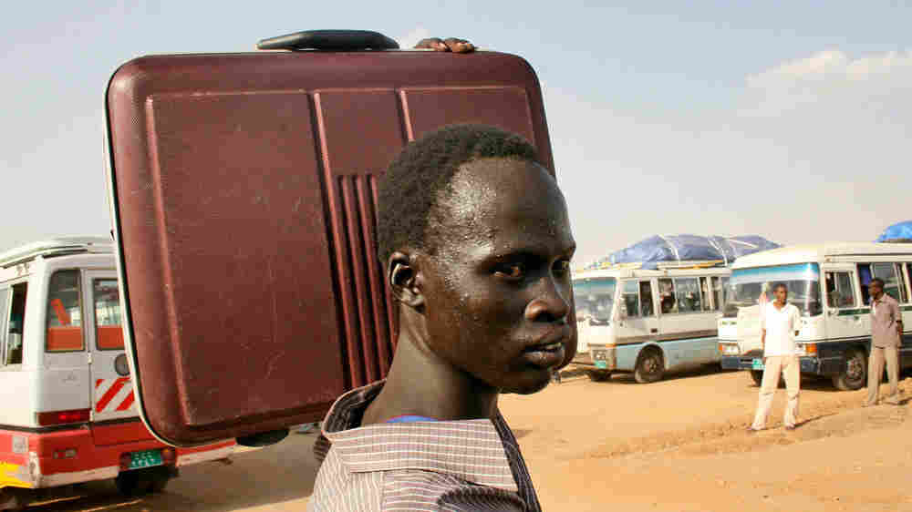Southern Sudanese man waits to board a bus that will take him from Khartoum to Southern Sudan