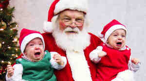 Santa holds crying babies.