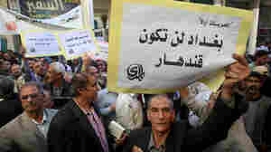 "An Iraqi man holds a sign reading ""Baghdad will not be Kandahar"" in Arabic as he takes part in a protest in Baghdad."