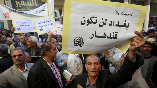 """An Iraqi man holds a sign reading """"Baghdad will not be Kandahar"""" in Arabic as he takes part in a protest in Baghdad."""
