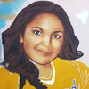 Tanya Lozoya's parents stand by a mural of their daughter in her softball uniform, painted in the backyard of their home near El Paso, Texas