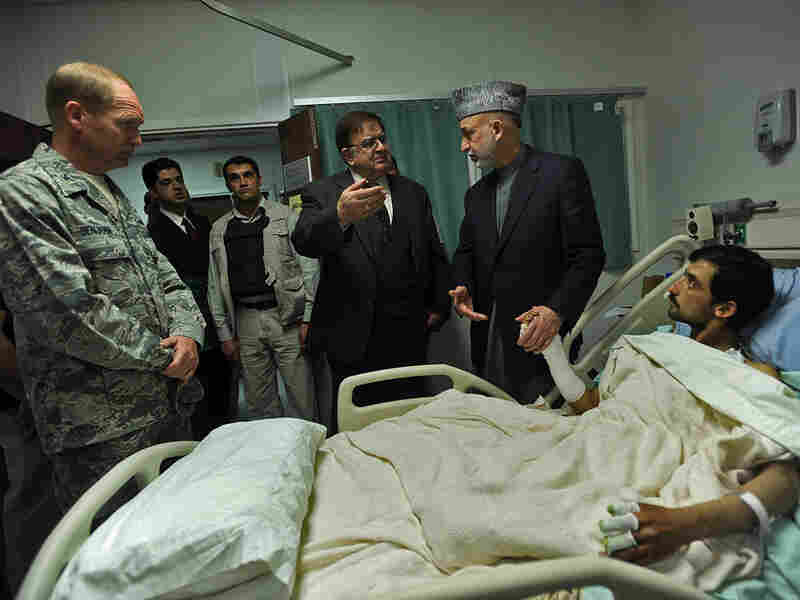 Afghan President Hamid Karzai (standing, right) talks to his defense minister, Abdul Rahim Wardak, as he visits a wounded Afghan National Army soldier.