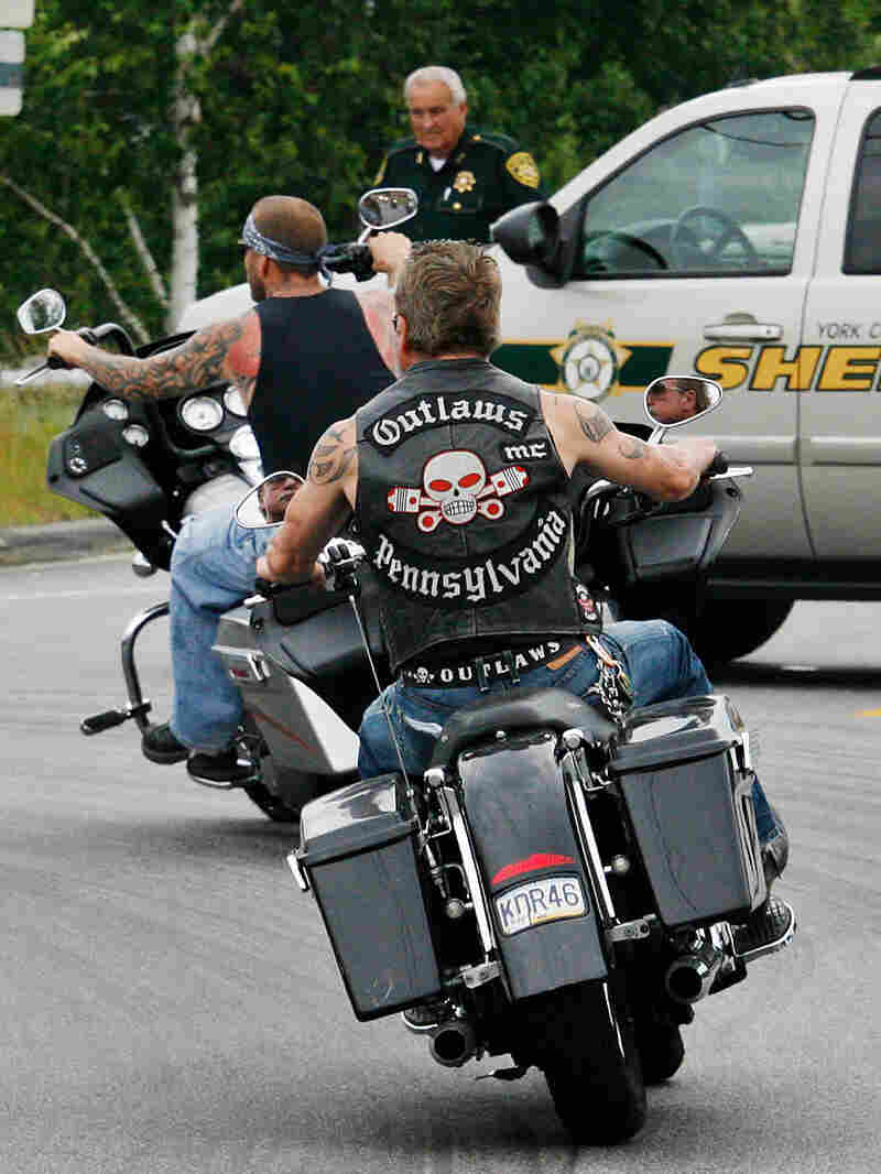 Members of the Outlaws motorcycle club pass a roadblock as they ride through Hollis Center, Maine.
