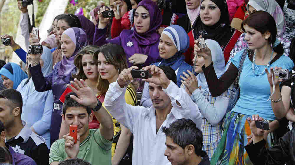 Iraqi university students take photos as they celebrate during their graduation party April 26, 2009, at the University of Technology in Baghdad