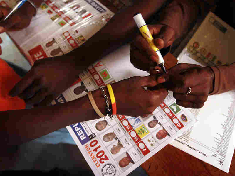 A poll worker places a mark on a voters hand to indicate she voted during Haiti's national election in Port-au-Prince, Haiti.
