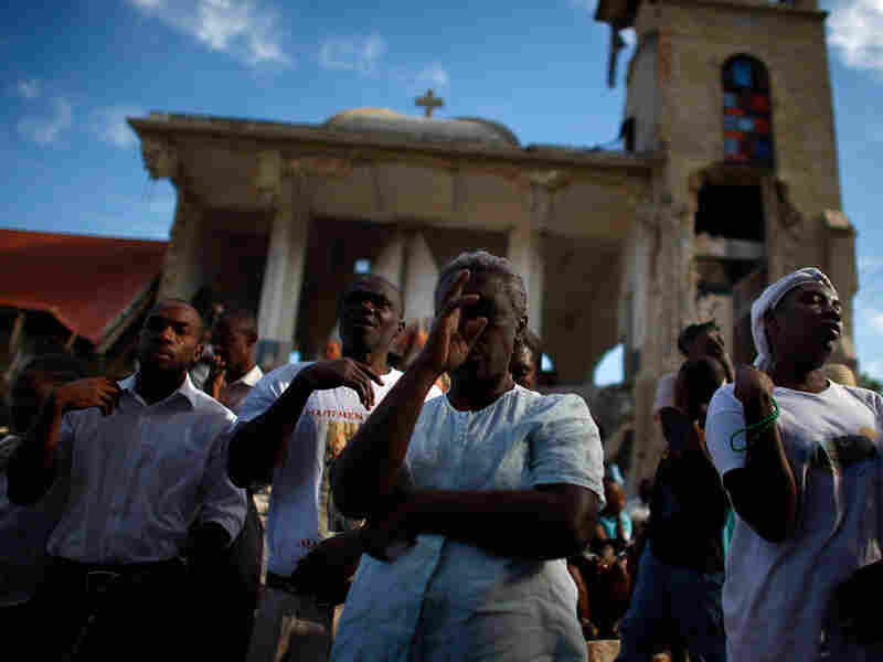 Haitians pray in front of the collapsed Sacre Coeur Church in Port-au-Prince