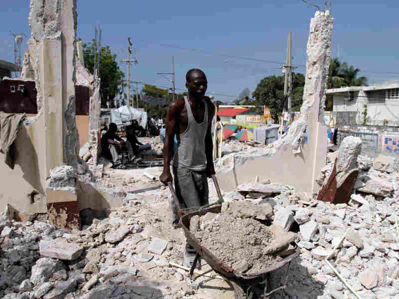 A Haitian man removes debris from a house damaged by the Jan. 12 earthquake in Port-au-Prince.