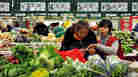 Chinese customers shop at the vegetable section of a supermarket in Beijing