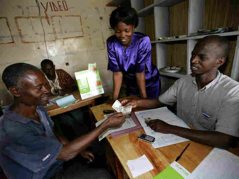 An M-PESA agent helps a client complete a transaction