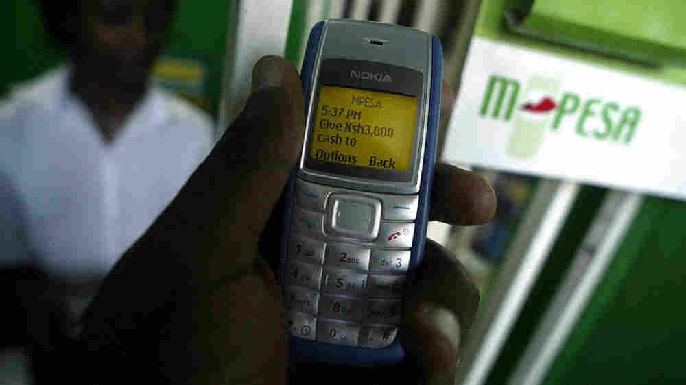 A man sends money through M-Pesa