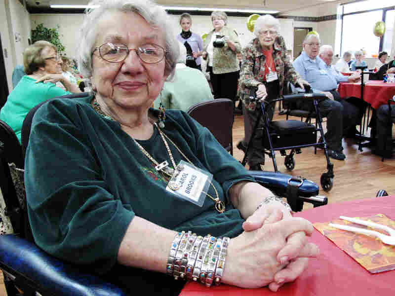 Mentor Carol Brooks, 72, wears a charm bracelet engraved with the names of the many refugees she's helped in the past decade.