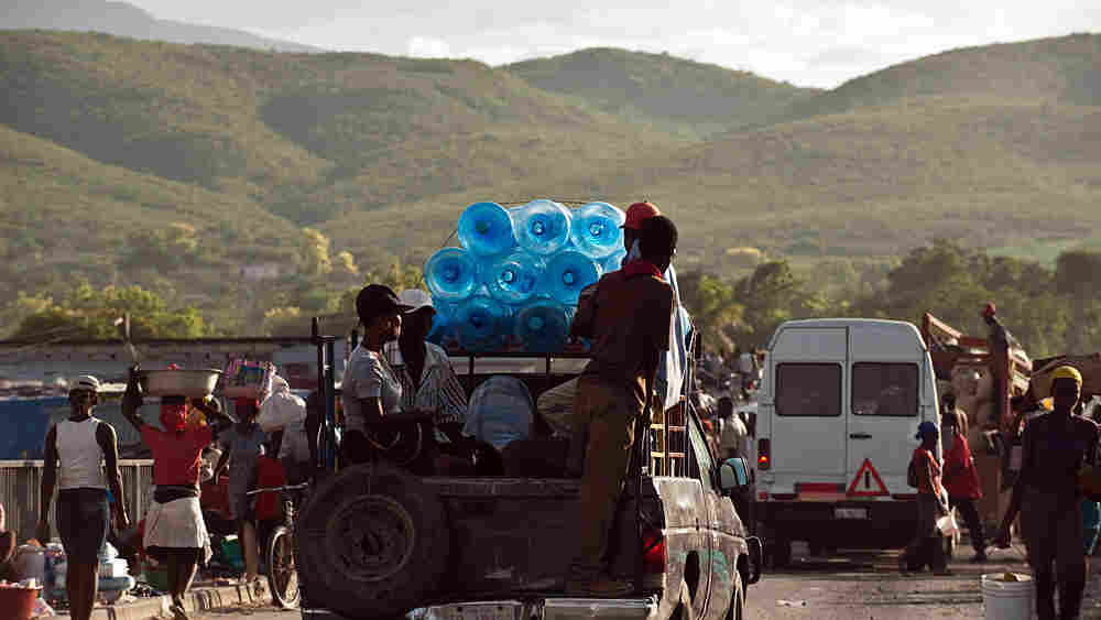 Empty water containers are transported on the back of a pickup truck at a market north of Port-au-Prince on Oct. 27, 2010.