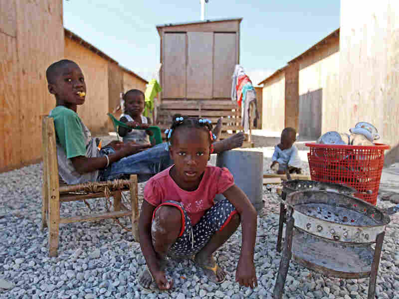 Children play in front of latrines built by the American Red Cross