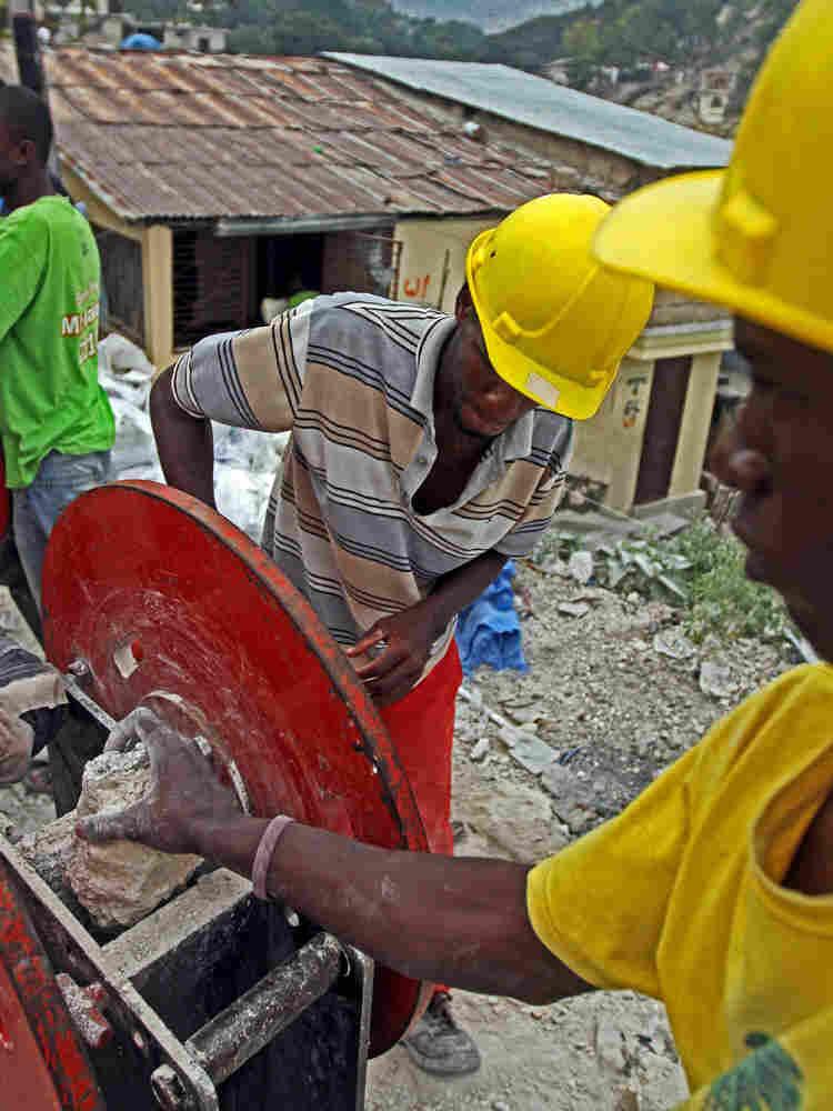 Men crush rubble.