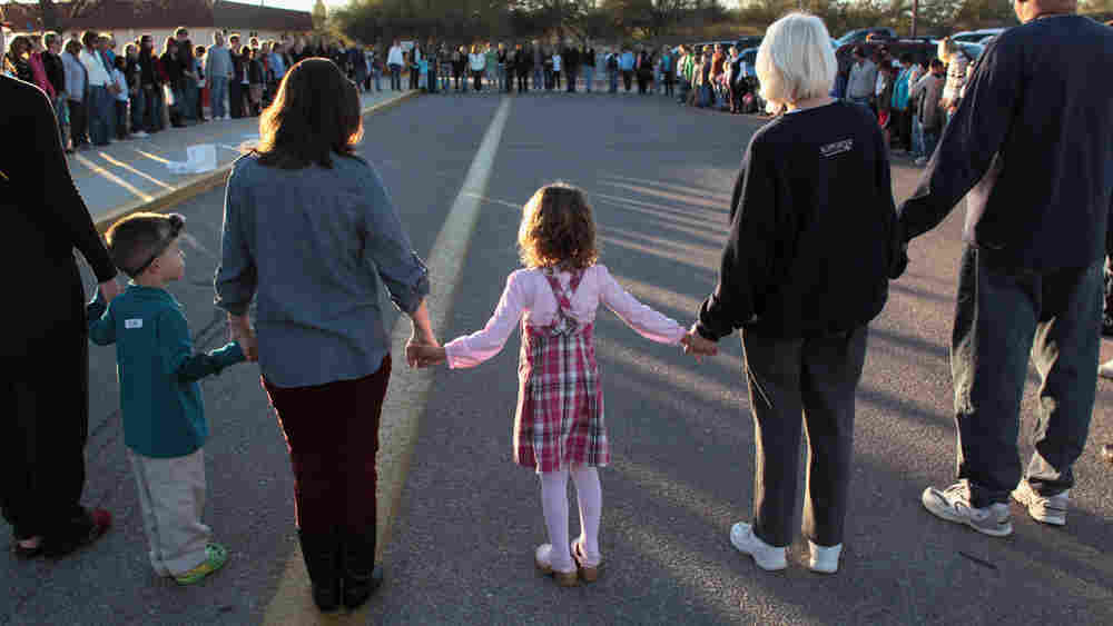Rachel Crabb (center), 5, holds hands with teachers, parents and other students during a moment of silence for her slain schoolmate Christina Taylor Green