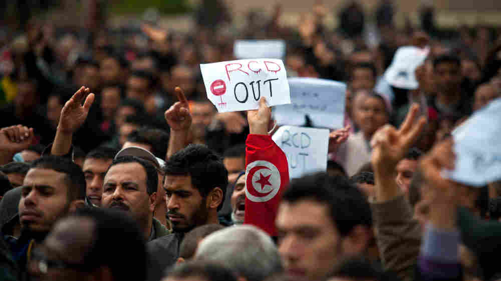 "A protester holds a placard reading ""RCD Out"" during a demonstration outside the headquarters of ousted Tunisian President Zine El Abidine Ben Ali's Constitutional Democratic Rally party in central Tunis."