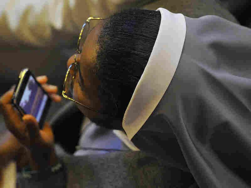 A nun holds a cell phone