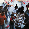 Bahraini protesters run for cover from tear gas fired by police in the village of Sanabis near the capital city, Manama, on Tuesday.