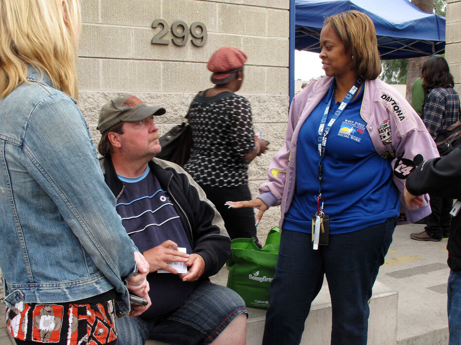 Homeless veteran Patrick Sean Williamson talks with VA social worker Marsha Latham (right) and case manager Carolyn Vahoviak (back to camera) outside a day center for homeless people in San Diego.  Williamson was homeless for about three years and suffers from diabetes.  The VA workers said they could help him find a place to live. (NPR)