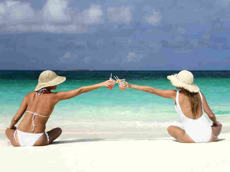 Two women share cocktails on a beach.