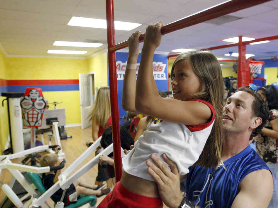 A girl does a pull-up with the help of her instructor.