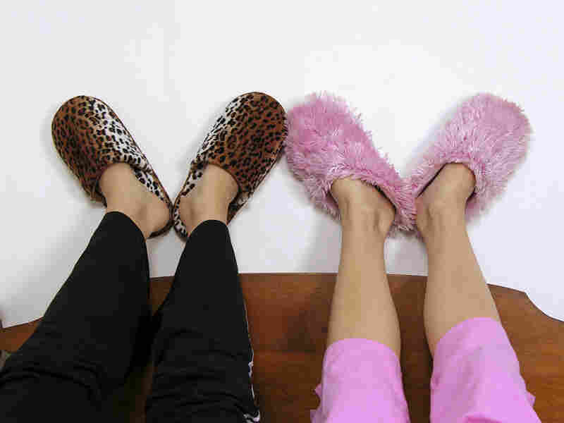 An image of friends slippers as they lie on a bed chatting.