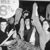 Women hold up nylon stockings in a sale in the 1950s.