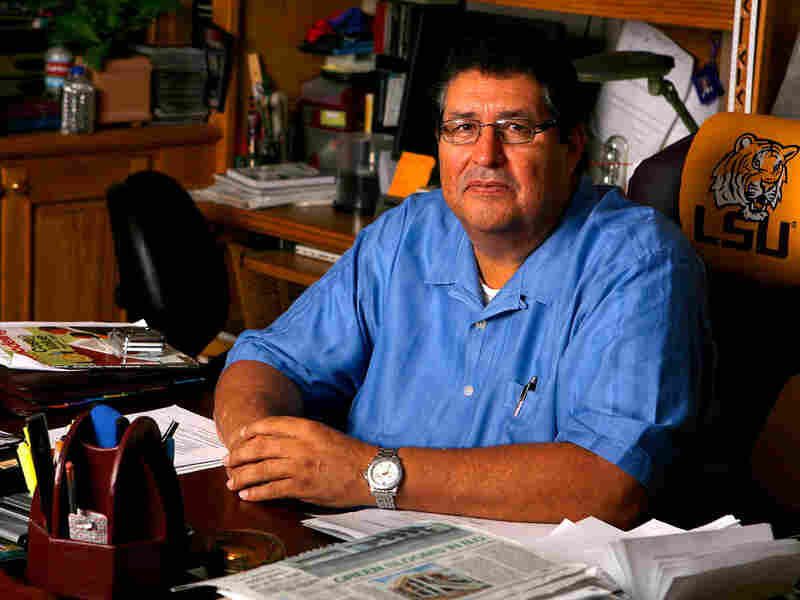 Fernando Arriola sits at the desk of the contracting business he owns.
