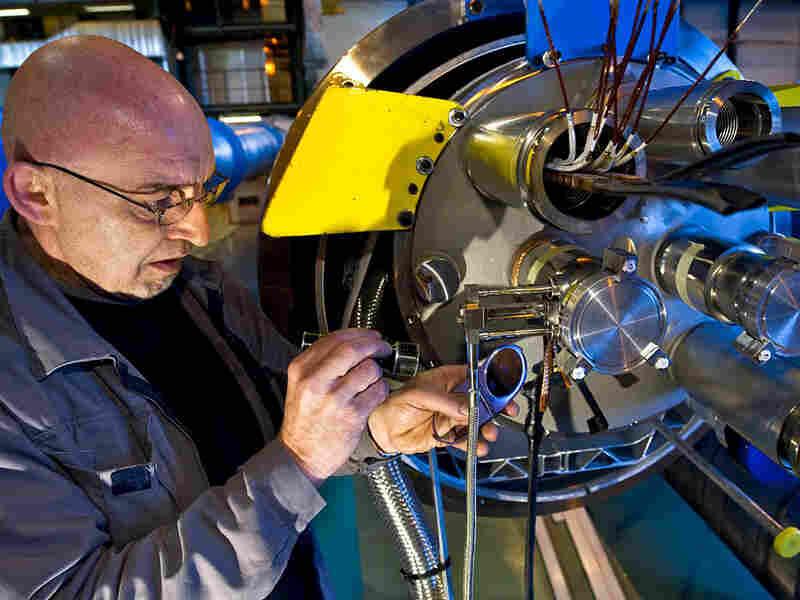 CERN scientist works on machinery.