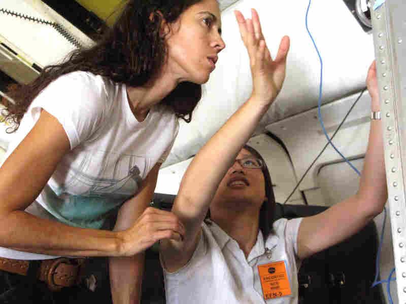 Graduate student Kamil Armaiz-Nolla (left) and Min Huang work aboard the airborne NASA laboratory.