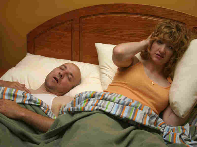 A wife tries to block out her husband's snoring with a pillow over her ears.