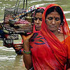 Bangladeshi women make their way through flood water at Dhakuria in Sirajgonj district.