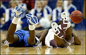 The heels of four basketball players are shown as they chase a loose ball.