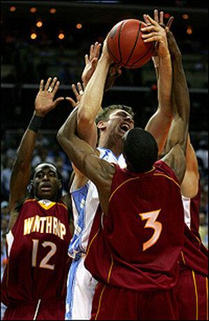 Winthrop's Torell Martin, Mantoris Robinson guard UNC's Tyler Hansbrough.