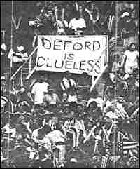 Soccer fans at RFK stadium in Washington, D.C., holding a sign that says, 'Deford is clueless.'